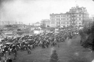 """A gathering on the causeway in front of the Empress Hotel in Victoria for the arrival of Father Christmas; note the advertisements for Rainier Beer and Coca Cola."" [1915]. Image B-07231/RBCM&A"